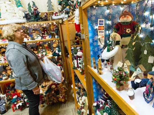 Norma Hood, of Las Cruces, browses items at Sally Day's booth on Saturday, December 3, 2016, during the 26th annual La Casa Holiday Bazaar at the Las Cruces Convention Center. Day's booth featured various snowmen and other festive handmade items.
