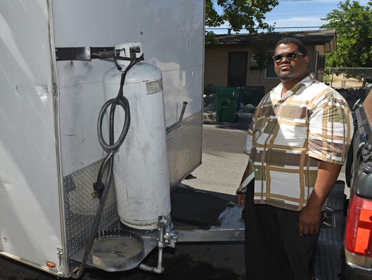 Stephon VanDyke stands next to his food truck where