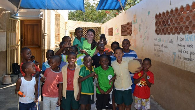 Aislinn McIlvenny stands with kids in Namibia during the organization's trip there in 2016 to donate goods.