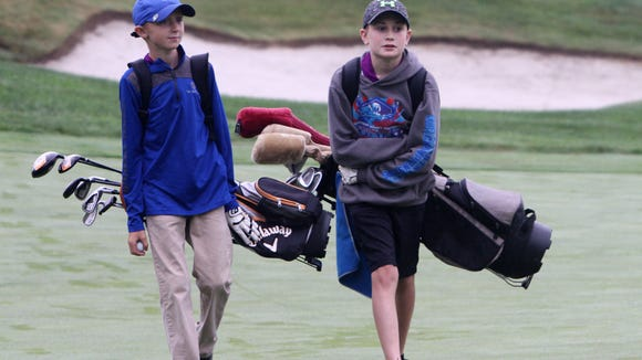 From left, Owen Lane and Liam Dima walk up the fairway