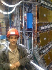 Iowa State University physics professor John Cochran stands next to the opened ATLAS detector during a shutdown period for the experiment at the Large Hadron Collider at CERN in Switzerland.