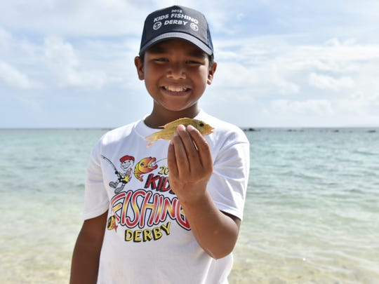 Competitor Damien Joseph Palomo holds up his catch at the 2018 Kid's Fishing Derby in Asan Park Beach on June 16, 2018.
