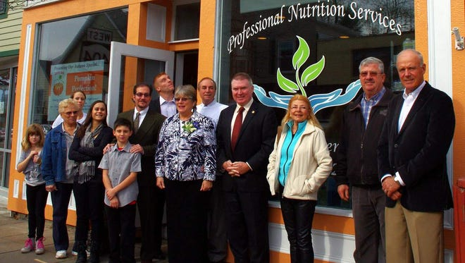 Local and state officials join Professional Nutrition Services owner Marge Pickering-Picone for the grand opening.