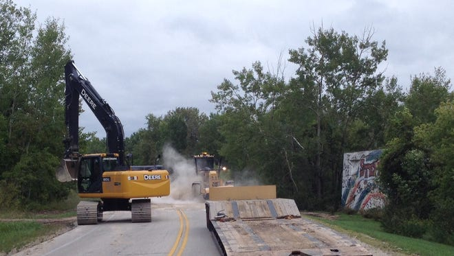 Door County Highway Department workers Thursday rebuild a stretch of County B where an old mining tunnel collapsed after recent rains.