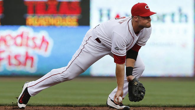 Cincinnati Reds shortstop Zack Cozart (2) flips to second base to start a double play in the third inning during the MLB game between the Chicago Cubs and Cincinnati Reds, Monday, June 27, 2016, at Great American Ball Park in Cincinnati.