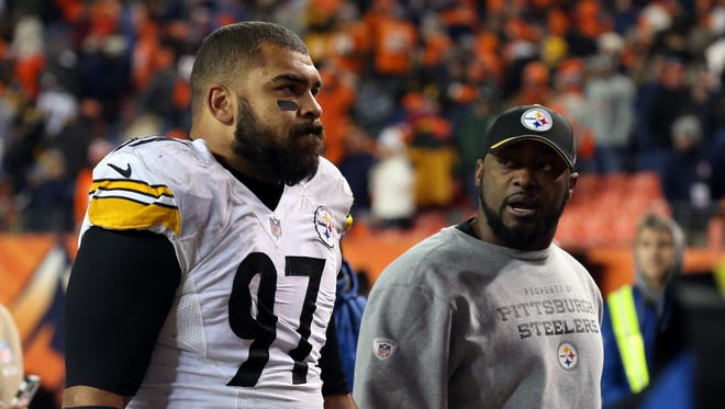 Pittsburgh Steelers defensive end Cameron Heyward (97) and head coach Mike Tomlin walk off the field after the AFC Divisional round playoff game against the Denver Broncos at Sports Authority Field at Mile High.