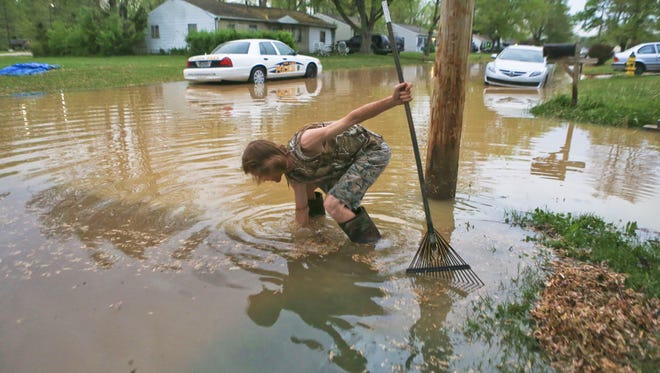 Steve Amburgey, a resident on Rhonda Drive in Jeffersonville, works to clear a drain after a water main break on 10th Street caused flooding early Thursday morning. Jeff fire department went house to house to check on residents in the area.