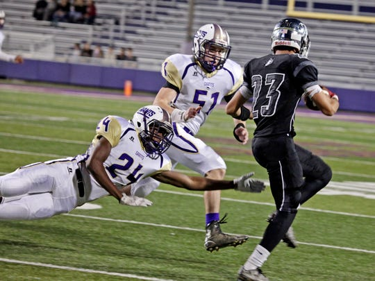 Waynesboro's Shaheim Johnson, left, dives for Turner Ashby's Michael De la Cruz as Waynesboro's Kerry Showalter goes for a tackle during the first half of the game against Turner Ashby on Friday, Oct. 14, 2016 at James Madison University's Bridgeforth Stadium in Harrisonburg.