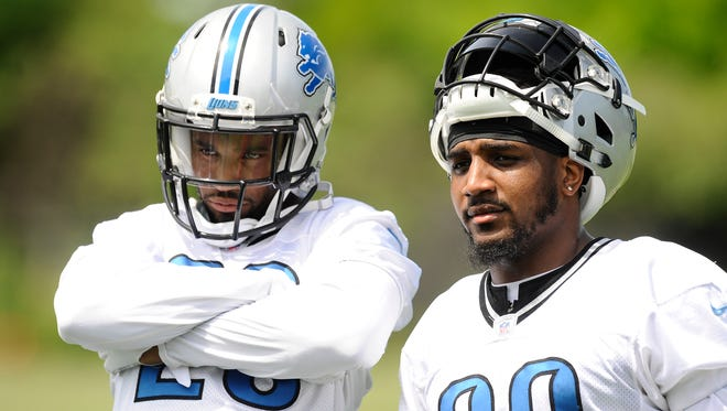 Cornerback Darius Slay and Crezdon Butler wait patiently, somewhat, to get their turn on the football passing machine Thursday.