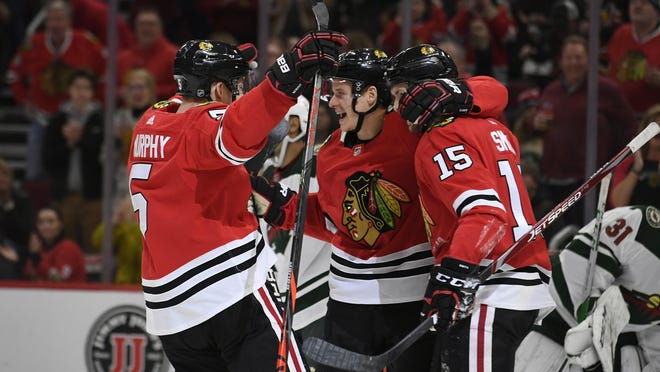 Chicago Blackhawks' David Kampf center, celebrates with teammates Zack Smith (15) and Connor Murphy (5) after scoring a goal during the second period of an NHL hockey game against the Minnesota Wild, Sunday, Dec. 15, 2019, in Chicago.