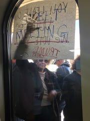 """A Donald Trump supporter presses a sign reading """"secret"""