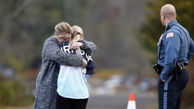 A woman who police identified as a friend of the victim is consoled by another woman on the long driveway that leads to the rear of the Foggia Florist and Greenhouses in Oceanport, NJ, where the body of Joseph Comunale, a 26-year-old Hofstra University graduate originally from Connecticut, was reportedly found Wednesday, November 16, 2016.