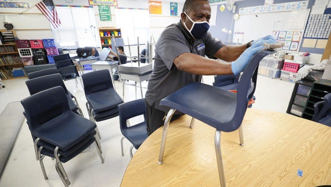 Custodian Tracy Harris cleans chairs in a classroom July 8 at Brubaker Elementary School in Des Moines, Iowa.