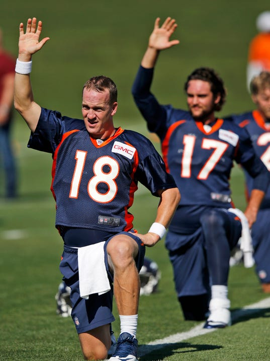 Denver Broncos quarterbacks Peyton Manning (18) and Brock Osweiler (17) stretch  during the first day of NFL football training camp on Thursday, July 24, 2014, in Englewood, Colo. (AP Photo/Jack Dempsey)