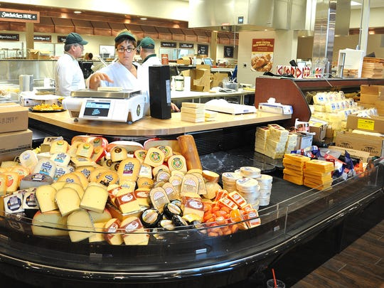 Lisa Green helps to get the cheese department ready