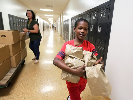 Giovanni Stanford, 10, helps Tawanna Applegate, a para professional, deliver Power Packs from the Freestore Feedbank to students at Oyler School in Lower Price Hill. During the school year, the packs go to 175-200 students on Fridays to feed the kids over the weekend.