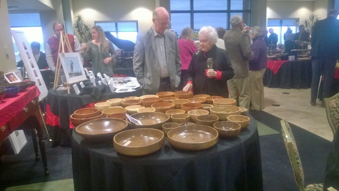 At last year's Valentine's Afternoon with the Arts, Jo Jenkins looked over bowls with woodcarver Terry Ellis. This year's event, hosted by the Clarksville/Montgomery County Arts and Heritage Development Council and F & M Bank, will be Sunday, Feb. 14, in the bank's Franklin Room.