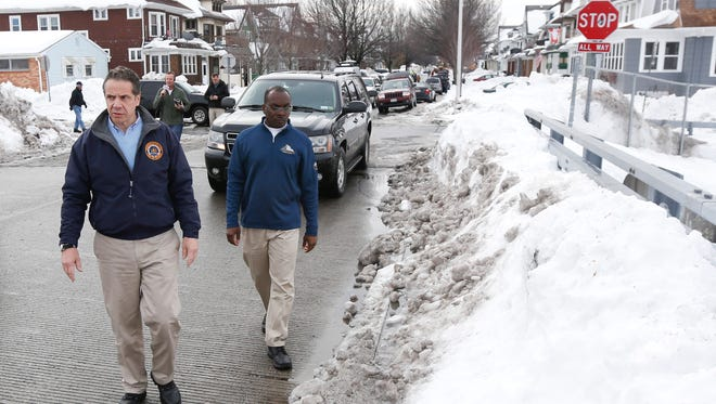 New York Gov. Andrew Cuomo, left, and Buffalo Mayor Byron Brown survey storm clean-up in the south Buffalo, N.Y. area on Sunday, Nov. 23, 2014. Western New York continues to dig out from the heavy snow dropped this week by lake-effect snowstorms. (AP Photo/Mike Groll)