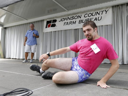 Sam Watts of North Liberty lays out on the stage Tuesday, July 28, 2015, as he competes in the Mr. Legs competition at the Johnson County Fair in Iowa City.