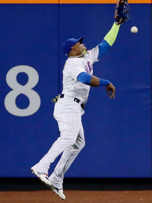 New York Mets left fielder Yoenis Cespedes leaps for a ball hit by Philadelphia Phillies' Maikel Franco for an RBI double during the third inning of a baseball game Thursday, April 20, 2017, in New York. (AP Photo/Frank Franklin II)
