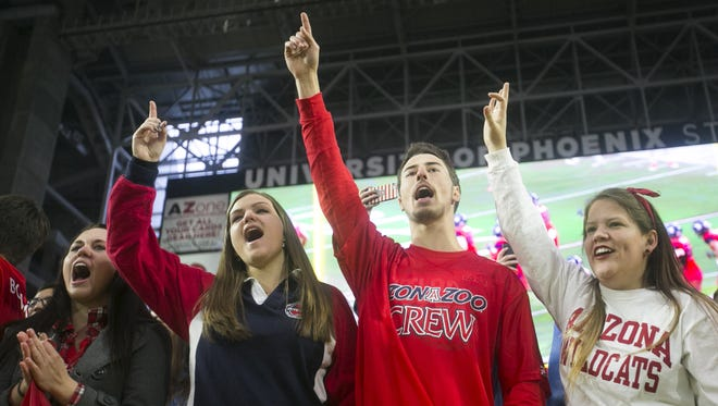 UA students Shannon Higgins, Emily Clearwater, Jason Teich and Madison Truman cheer before the start of the Fiesta Bowl between Boise State and Arizona on Wednesday, December 31, 2014.