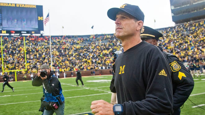 Michigan head coach Jim Harbaugh walks the field toward the Oregon State sideline after the fourth quarter of an NCAA college football game against Oregon State in Ann Arbor, Mich., Saturday, Sept. 12, 2015. Michigan won 35-7.