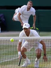 Mike Bryan, foreground, waits for the serve of partner