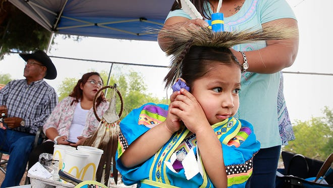 Tyren Yeba, 4, of Farmington, tries to hear his toy over the din of drumming while his mom, Tomelina Castillo, gets him ready for the junior boys Grass Dance at the Totah Festival Indian Market & Pow Wow on Sept. 3 at the Farmington Civic Center. The event returns to the civic center this weekend.