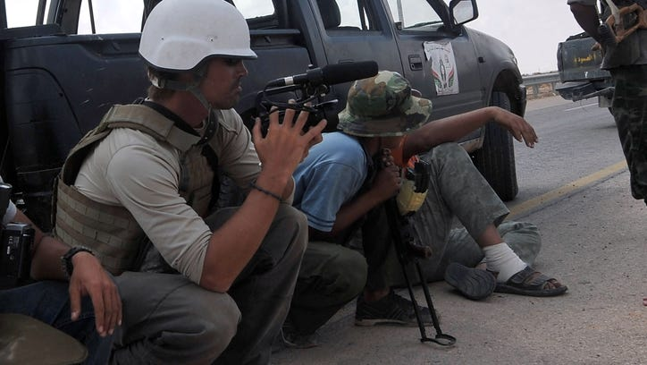 A photo taken on September 29, 2011 shows freelance reporter James Foley, left, on the highway between the airport and the West Gate of Sirte, Libya.