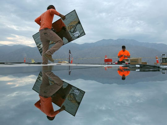 Charlie Quezada, left, and Anzony Gonzalez install solar panels at the Palm Springs Air Museum on Sept. 10, 2015.