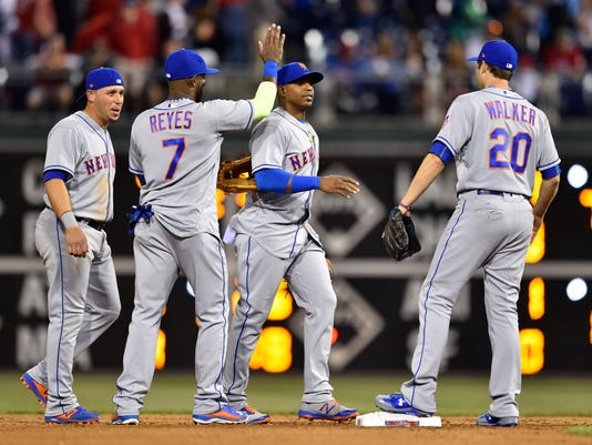 New York Mets' Yoenis Cespedes, second from right, celebrates with Jose Reyes (7), Neil Walker (20) and Asdrubal Cabrera, left, after the Mets' 5-4 win over the Philadelphia Phillies in a baseball game Wednesday, April 12, 2017, in Philadelphia. (AP Photo/Derik Hamilton)