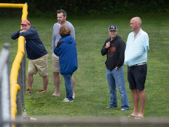 Some parents watch from over outfield fence. Two River