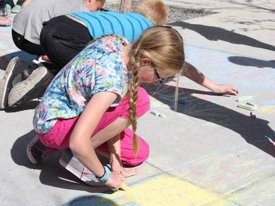 Students using chalk to tell stories