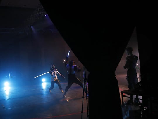 A man watches competitors as they battle during a national lightsaber tournament in Beaumont-sur-Oise, north of Paris. ""