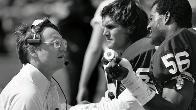 Cleveland Browns head coach Marty Schottenheimer talks to linebackers Clay Matthews (57) and Chip Banks (56) during the 1985 AFC Divisional Playoff Game against the Miami Dolphins at the Orange Bowl. Miami defeated Cleveland 24-21.