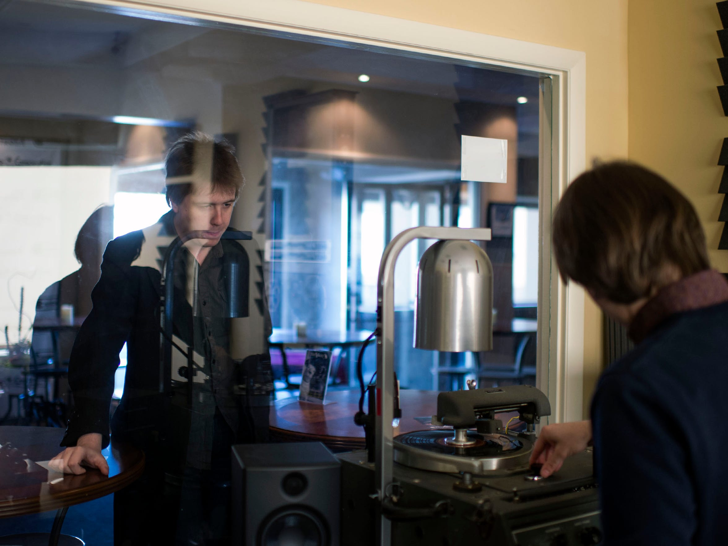 Graham Alexander, left, observes as Zach Harski fires up their record lathe at The Vault in Berlin.
