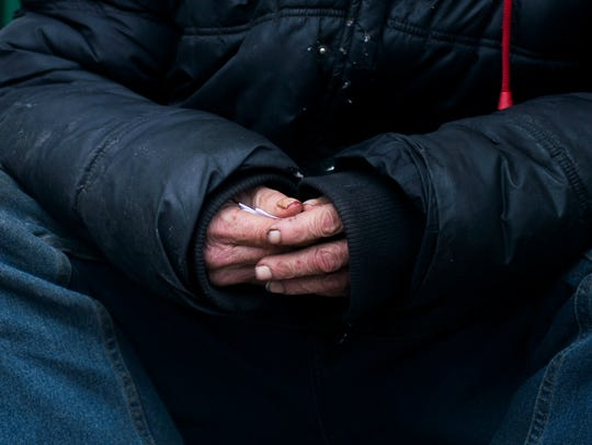 A homeless man sits on a stoop on E. Commerce Street in Bridgeton in this file photo.