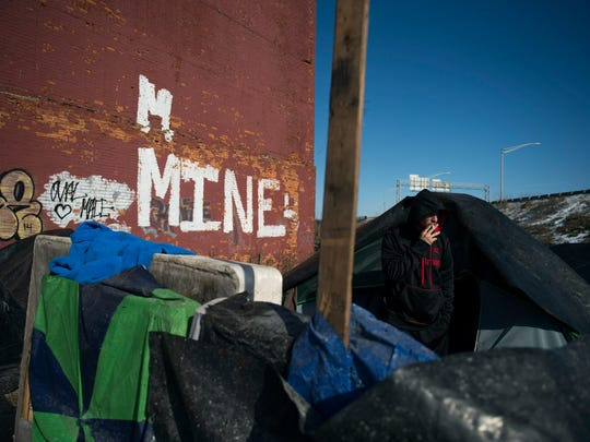 Michael Allen, 23, a homeless man originally from Woodbury, smokes a cigarette outside his tent by an abandoned building off S 7th St near the intersection of Mechanic St Wednesday, Jan. 27 in Camden.