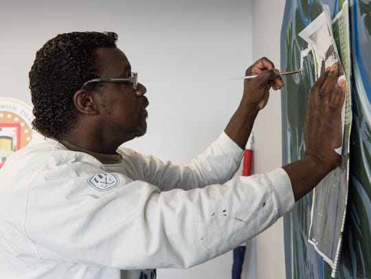 James Collins paints a mural of Smith Island in the