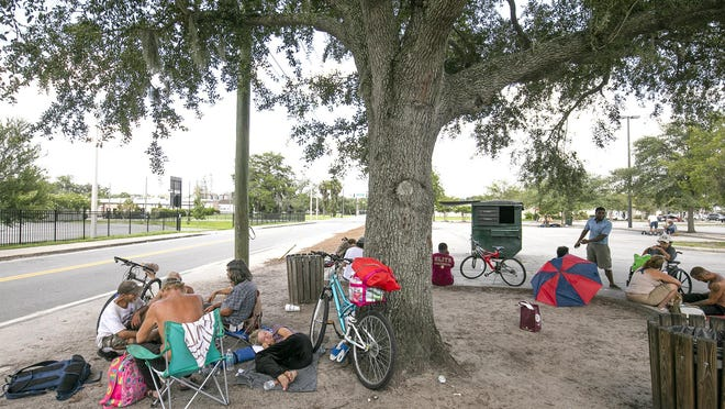 The homeless congregate in the parking lot at Northwest First Avenue and Third Street in Ocala on Thursday afternoon.They sleep and eat in the corner of a public parking lot. The behavior is seen as a stumbling block to continued redevelopment of the area. The city hopes to confer with community agencies and figure out a grand plan to address the concerns.