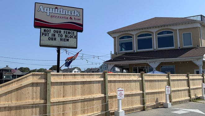 The management of Aquidneck Pizza aren't pleased with a 6-foot fence that was erected by abutting restaurant Tickets Bar & Grille, saying it blocks the ocean view of diners.