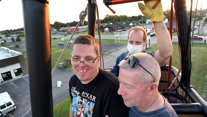 With help from his father, Clyde William Jenkins (center) of Monroe, a wheelchair user, stood during a hot air balloon ride to soak in the experience. The elder Clyde Jenkins (right) supported his son, along with pilot Larry Coan. The event, organized for individuals with disabilities, was held Friday by 2 42 Community Church of Monroe.