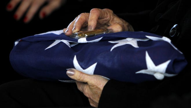 Helen Carter, the wife of James A. Carter holds the flag that covered her husband's casket as he was laid to rest.