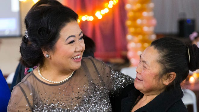 Blia Cha (center) greets well-wishers during her retirement party Saturday at Milwaukee's Asian Market, 6300 N. 76th St., in Milwaukee. Several hundred people turned out for the party.