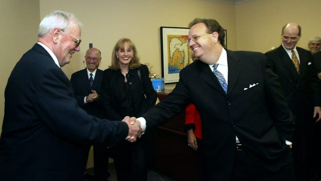 Jack Norman Jr. is greeted by Philip Smith and others after Norman walked into a surprise party for him in 2003. The party recognized Norman as he was leaving private practice to be the special master of the Fourth Circuit Court.