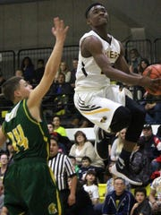 Alamogordo's Kamiron Bickham soars toward the basket while being guarded by Mayfield's Jorge Cadena.