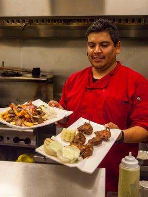General manager Octavio Mejia displays a couple of menu options at Pisco Peruvian Cuisine.