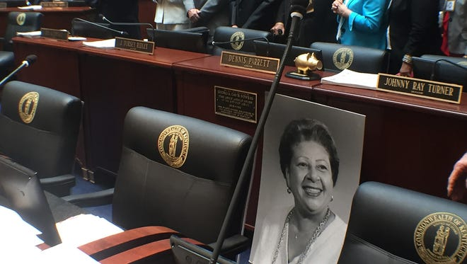 A vintage photo of the late Georgia Powers sits next to her desk where a state worker moments before installed a plaque honoring her.
