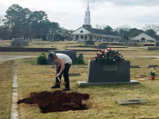 A cemetery worker tends to the Lee family plot, where