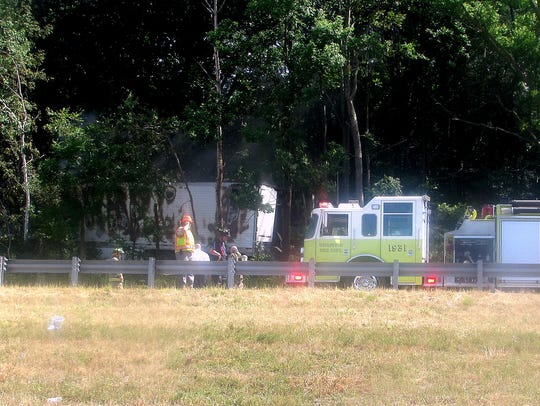 Firefighters stand near a tractor trailer that crashed